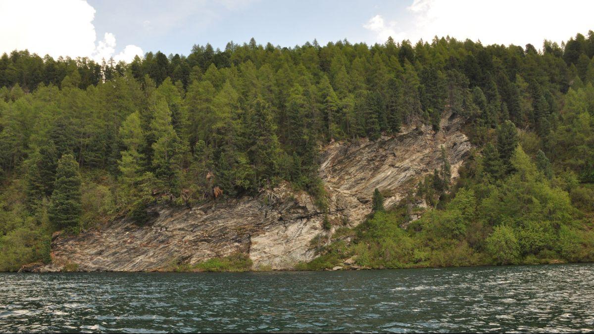 Dieser massive Felsbrocken zwischen Sils und Isola steht beiden Verbindungsvarianten im Weg. Er muss entweder überwunden werden (oberes, bisheriges Trassee) oder über einen verankerten Steg oberhalb der Wasserfläche umrundet werden (neue untere Variante)