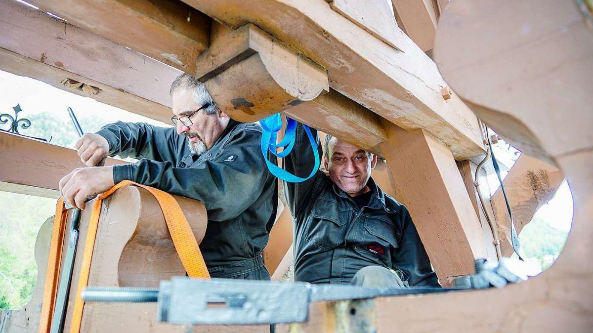 Die Monteure der Firma Muff Kirchturmtechnik AG, José Benitez (links) und Charles Pürro, befestigen die alten, geschmiedeten und jetzt neu konservierten Aufhängebänder der Pontresiner Kirchenglocken wieder. Foto: Jon Duschletta