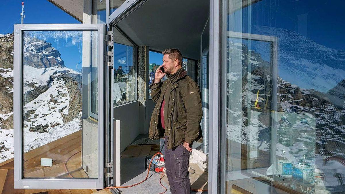 Pascal Mittner am Eingang zur Orma-Whisky-Destillerie auf der Corvatsch-Bergstation. Er erfährt gerade am Telefon von seinem Geschäftspartner Rinaldo Willy, dass an diesem Dienstag keine Heliflüge stattfinden können. Foto: Jon Duschletta