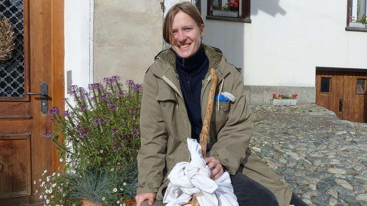 L'artista Sophie Innmann sül banc davant porta, pronta pel discuors e la lavur artistica (fotografia: Flurin Andry).