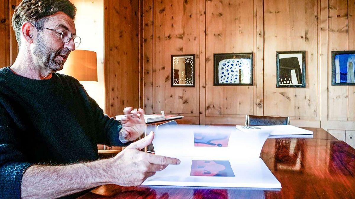 Hans Schmid alias Bastiann blättert in der Stüva der Chasa Bastiann, umgeben von seinen Bildern, im neuen Werkbuch «Elefantul». Foto: Jon Duschletta