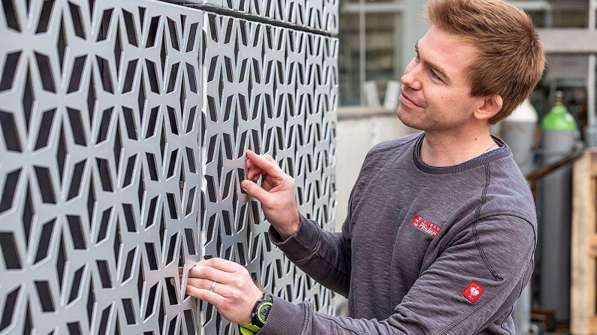Fassadenspezialist Curdin Pfister begutachtet eine frisch geschnittene Lochplatte in der Werkstatt in Samedan. Foto: Daniel Zaugg