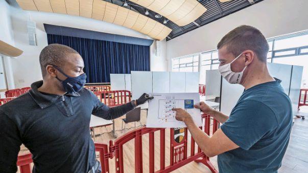 George Manasi (links) und Gabriel Staub von der Gemeinde Pontresina besprechen letzte Details für den Aufbau des Testcenters im Rondo. Foto: Daniel Zaugg