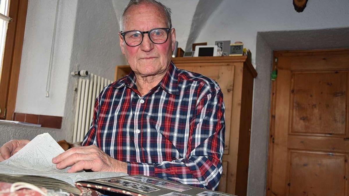 Gion Denoth da Zernez as regorda sfögliand l'album da fotografias da la tragedia dals 19 schner 1951 (fotografia: Nicolo Bass).