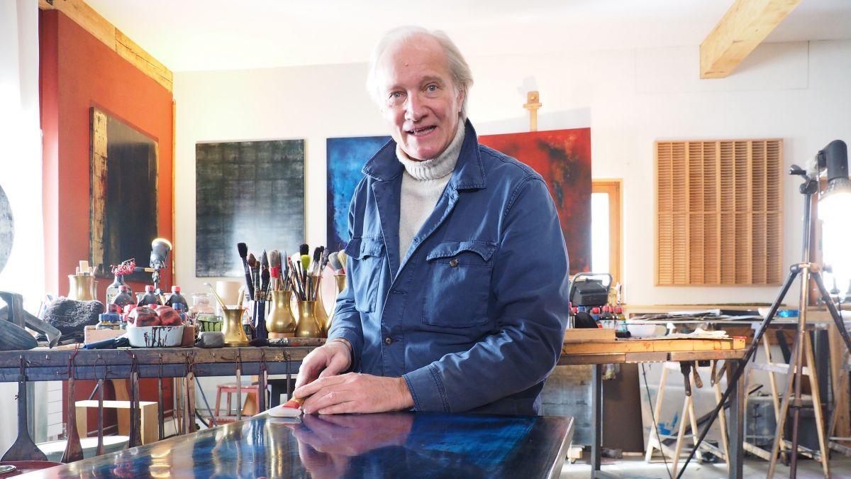 André Piot inmitten seines Ateliers beim Polieren eines Bildes mit einem Agatstein