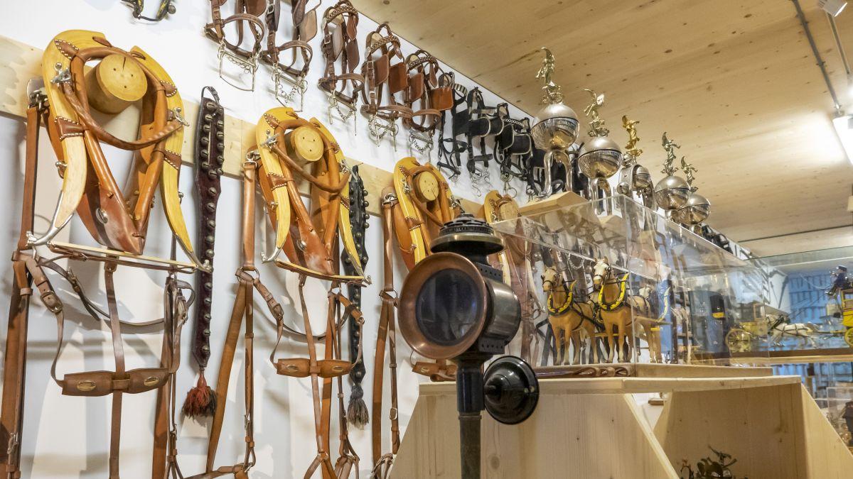 Bündner Geschirre an der Wand, diverse Kutschenlampen, Halfter und auch ein Postkutschen-Modell sind Teil der Sammlung.