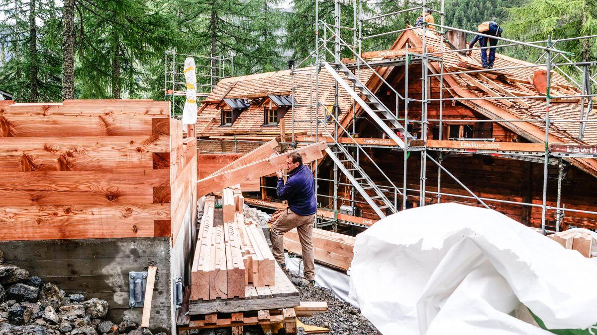 Umbau der Chamonna Cluozza: Links entsteht ein neuer Personal-Schlafturm und rechts wird das Haupthaus mit neuen Lärchenschindeln eingedeckt. Die Eröffnung ist für Juni 2022 geplant. Foto: Jon Duschletta