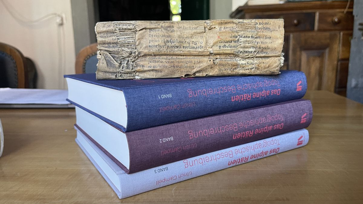 Units illa biblioteca – ils trais toms da la nouv'ediziun insembel cul manuscrit original, illa biblioteca von Sprecher a Maiavilla (fotografia: Isabelle Jaeger/RTR)