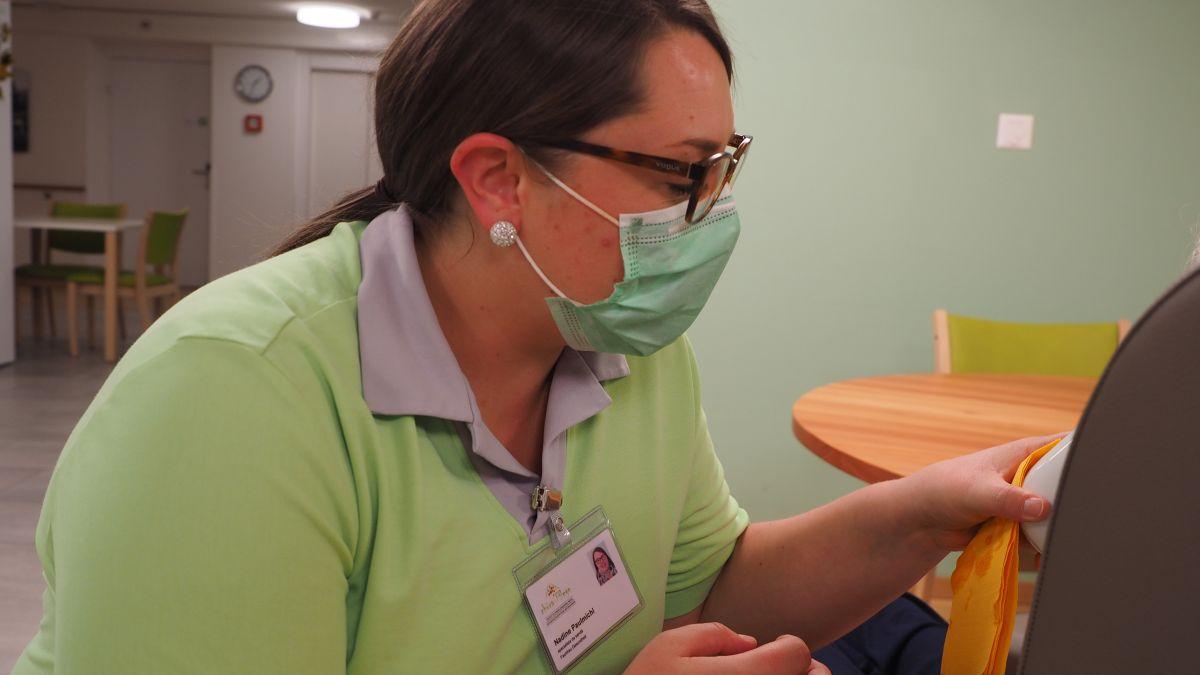 Gehört zu täglichen Arbeit im Pflegeheim Puntota in Scuol: Nadine Paulmichl flösst einer Bewohnerin etwas Tee ein. Foto: Marie-Claire Jur