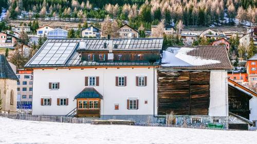 Südansicht des Hauses Schucan in Zuoz mit unterschiedlichen Dachmaterialien, thermischer Solaranlage, Küchenlaube aus den 1940er- und Dachgaube aus den 1960er-Jahren sowie dem Heustall, der zu Erstwohnungen umgebaut werden soll. Das Stalldach soll eine