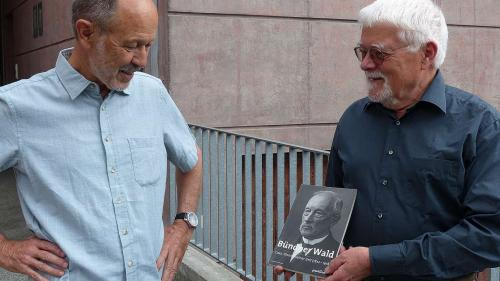Jon Duri Tratschin (a schnestra) e Paul E. Grimm cun üna publicaziun davart il silvicultur Johann Coaz davant la chasa da scoula a Strada. fotografia: Flurin Andry