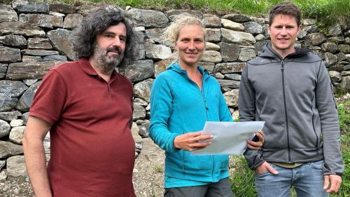 Johannes Florin, Lisa Zimmermann e Nicolas Ilg (da schnestra) davant il mür sech a Cha Noschas chi'd es gnü renovà (fotografia: Angelika Abderhalden).