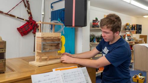 Gian Andrea Caratsch erklärt, wie das Miniaturmodell einer Orgel, das er selbst gebaut hat, funktioniert.  Fotos: Valentina Baumann