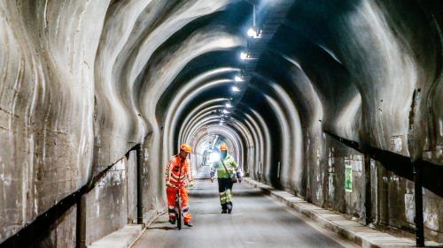 Bauarbeiter unterwegs im Tunnel Munt la Schera der Engadiner Kraftwerke AG. Gut zu erkennen sind die punktuellen Ausweitungen im Lichtraumprofil des Tunnels. Foto: Jon Duschletta